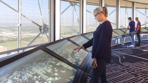 A visitor interacts with the observation deck touchscreen on Reunion Tower's GeO-Deck.