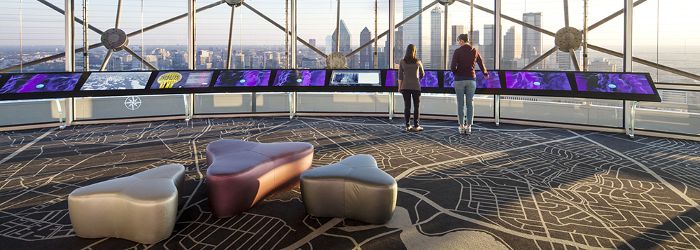 Visitors interact with the touchscreens on Reunion Tower's observation deck.