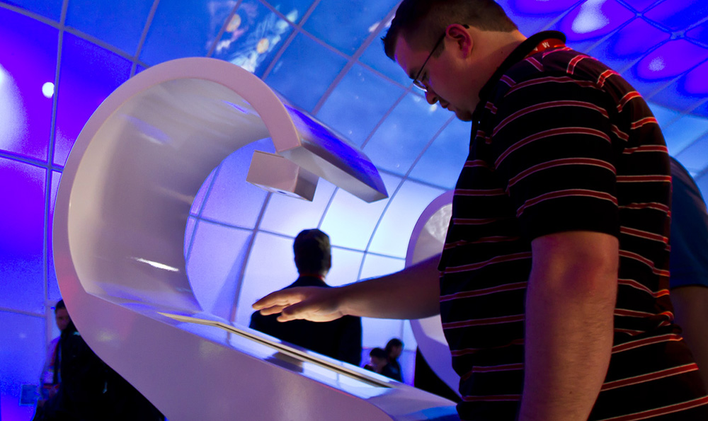 Person scanning hand at interactive station